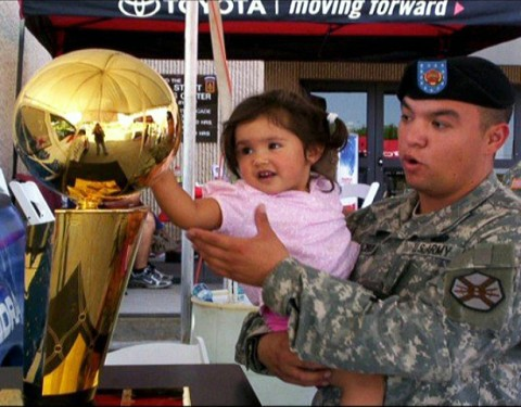 U.S. Army Staff Sgt. Gabriel Villalobos, a military intelligence analyst with Intelligence and Sustainment Co., Headquarters and Headquarters Battalion, 101st Airborne Division, holds his then 4-year-old daughter, Briana, while they check out an NBA trophy at Fort Bliss, Texas, in the summer of 2008. Villalobos is a U.S. citizen who grew up in a Mexican border town. He joined the U.S. Army to give back to the country that has given him so much. (Photo courtesy of U.S. Army)