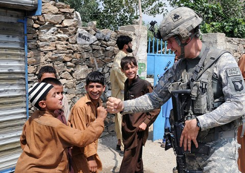 Kunar Province, Afghanistan - U.S. Army Pfc. Gary W. Faust of Bowling Green, Ky., a medic with 4th Platoon, Company D, 1st Battalion, 327th Infantry Regiment, Task Force Bulldog, practices his fist bump with children of Andersil village in eastern Afghanistan's Kunar province July 20th. (Photo by U.S. Army Staff Sgt. Gary A. Witte, 300th Mobile Public Affairs Detachment)