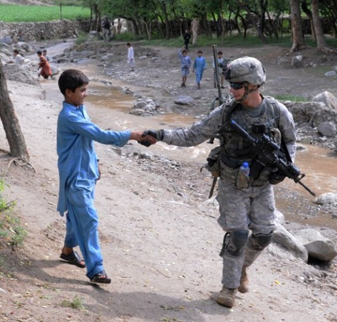 Kunar Province, Afghanistan, Afghanistan - U.S. Army Spc. Cory B. Petrosky of Grapevine, Texas, a radio operator with 1st Platoon, Company A, 1st Battalion, 327th Infantry Regiment, Task Force Bulldog, greets a youth outside the village of Shamir Kowt in eastern Afghanistan's Kunar province July 21. The unit, based at nearby Combat Outpost Honaker-Miracle, patrolled the area with Afghan National Police officers and surveyed business owners in the village bazaar about their concerns. (Photo by U.S. Army Staff Sgt. Gary A. Witte, 300th Mobile Public Affairs Detachment)