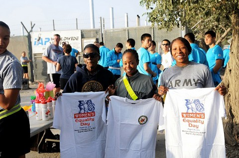 Two Soldiers and a Sailor show the commemorative T-shirt they each received at the completion of Bagram Airfield's Women's Equality Day five-kilometer run Aug. 26th. (Photo by U.S. Army Pfc. Roy Mercon, Task Force Wolverine Public Affairs)
