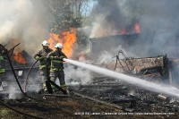 Firefighters hose down debris from the house to ensure that the grass fires do not reignite.