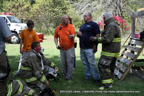 Captain William Jackson the Incident Commander (Center orange shirt) holds a conference with some of his men as they recover from their time fighting the fire.