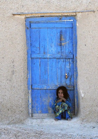 A village girl huddles near her home after an attack on Forward Operating Base Thunder, one of three bases insurgents attacked in eastern Afghanistan Sept. 24th. (Photo by U.S. Army Staff Sgt. Troy P. Johnson, 304th Public Affairs Detachment)