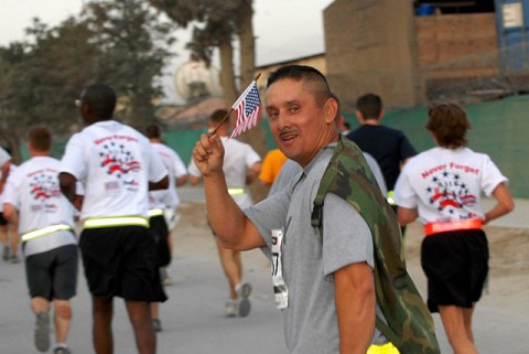 A Soldier deployed to Bagram Airfield waves his personal American flag while participating in the Patriots Day Run Sept. 11th. More than 2,200 deployed servicemembers and civilians ran 9.11 km in remembrance of the 9/11 attacks. (Photo by U.S. Army Capt. Michelle Lunato, 359th Theater Tactical Signal Brigade)