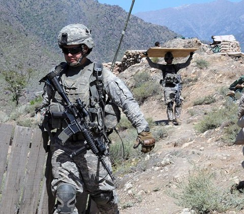 From left, U.S. Army Pfc. Dustin D. Riedemann of Lemars, Iowa, and U.S. Army Pfc. Dustin Wade of Mulberry, FL, with 1st Platoon, Company A, 1st Battalion, 327th Infantry Regiment, Task Force Bulldog, help move materials at a mountaintop observation post in eastern Afghanistan's Kunar Province Sept. 21st. (Photo by U.S. Army Staff Sgt. Gary A. Witte, 300th Mobile Public Affairs Detachment)