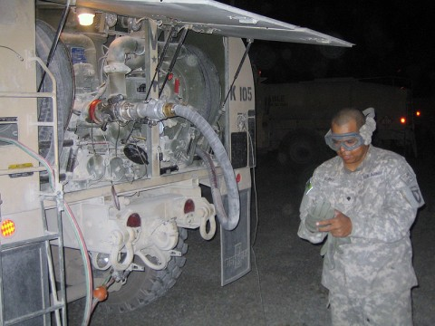 Spc. David P. Rubio, E Co., TF Shadow petroleum supply specialist, puts on his fire retardant gloves before checking the 2,500 gallons of fuel inside the Heavy Expanded Mobility Tactical Truck for water content and doing preventative maintenance to ensure that the night shift refuelers are able to safely conduct their mission on the flight line at Kandahar Airfield, Afghanistan.
