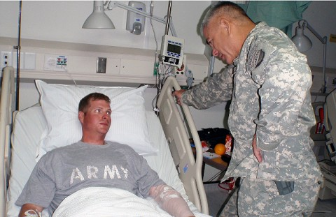 U.S. Army Maj. Gen. John Campbell, Commander of the 101st Airborne Division, stands over the bedside of U.S. Army Sgt. William Bickers Sept. 16th at Bagram Air Field in Afghanistan. Campbell presented Bickers with the Combat Infantryman's Badge for his direct engagement with the enemy and a Purple Heart for being wounded in the line of duty while on a foot patrol in Andar District, Ghazni province. (U.S. Army photo by 1st Lt. R.J. Peek)