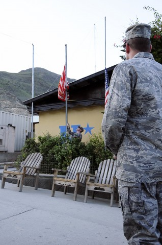U.S. Air Force Chaplain (Capt.) James Anderson, the chaplain for Forward Operating Base Wright, looks on, U.S. Navy Lt. Cdr. Sean Gillespie lowers the PRT flag to half-mast as part of a ceremony commemorating Patriot Day and the ninth anniversary of the Sept. 11th attacks. (Photo by U.S. Air Force Capt. Peter Shinn, 734th Agri-Business Development Team)