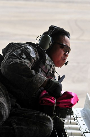 Chief Warrant Officer 2 David E. Fabunan, Task Force Strike jumpmaster, peers off the back ramp of a TF Shadow CH-47 Chinook helicopter waiting to perform a practice drop for the Pathfinders on the ground to confirm their accuracy.