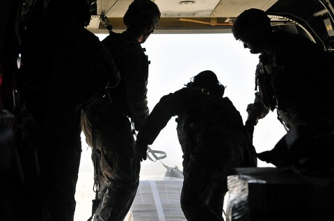 """The jumpmaster waits for the Chinook pilots to give the order to """"execute"""" the airdrop before pushing the bundle out the back of the aircraft. The Chinooks are equipped with """"Helicopter Internal Cargo Handling Systems"""", rollers, which allows for less force when dropping a bundle weighing over 200 pounds."""