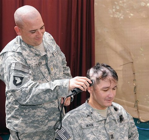 U.S. Army Maj. Richard Smith, assigned to 3rd Battalion, 320th Field Artillery Regiment, uses a pair of clippers to shave the head of U.S. Army Capt. James Wade, a native of St. Petersburg, FL, and civil affairs officer, 3rd Bn., 320th FA Reg., at Forward Operating Base Salerno here Sept. 4th.  The Soldiers have also raised money for the families to help ease their financial burden. (Photo by U.S. Army Sgt. Brent C. Powell, 3rd Brigade, 101st Airborne Division)