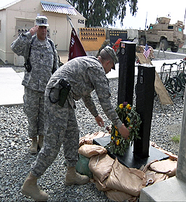 Soldiers of 334th Combat Support Hospital honoured their fallen Soldiers during a 9/11 remembrance ceremony at Forward Operating Base Salerno here Sept. 11. Laying the homemade wreath on a model of the twin towers is U.S. Army Lt. Col. Gregory Kolb, 344th CSH commander and a resident of Dacula, GA, as U.S. Army 1st Sgt. Jay Rippel Jr. renders a salute.  (Photo by U.S. Army Sgt. 1st Class Kenny Scott, 3rd Brigade, 101st Airborne Division Public Affairs)