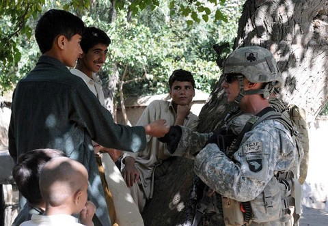 U.S. Army Spc. Robert E. Yates of New Orleans, a team leader with 3rd Platoon, Company D, 1st Battalion, 327th Infantry Regiment, Task Force Bulldog, gives a fist bump to a youth in Samatan village in eastern Afghanistan's Kunar Province Sept. 24th. (Photo by U.S. Army Staff Sgt. Gary A. Witte, 300th Mobile Public Affairs Detachment)