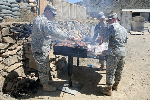 U.S. Army Lt. Col. David J. Preston, commander of 801st Brigade Support Battalion, 4th Brigade Combat Team, 101st Airborne Division and native of Belchertown, MA, rotates food on the grill as U.S. Army Sgt. Alison R. Macdonald, with the 801st Bde. Support Bn., 4BCT, 101st Airborne Div. and native of Gloucester, VA, places another round of steaks on the grill. (Photo by U.S. Army Spc. Luther L. Boothe Jr., Task Force Currahee Public Affairs Office)