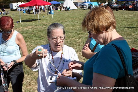 Vendor Philnese Slaughter shows some merchandise to one of the visitors to the Powwow