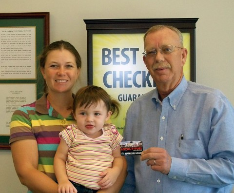 Planters Bank VP and Sango Branch Manager Fred Slack (right) presents a $100 Loyal-T-Fuel gas card to Cube finalist Penny Goddard and daughter Savannah.