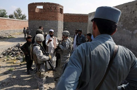 An Afghan National Policeman watches as Soldiers from the 330th Military Police Company meet with a village elder and discuss security concerns Oct. 7th. The Soldiers are working closely with approximately 300 ANP to help train and advise them on all aspects of law enforcement operations. (Photo by U.S. Army Staff Sgt. Brent C. Powell, 3rd Brigade, 101st Airborne Division)