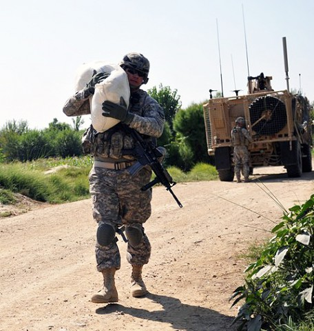 U.S. Army Sgt. 1st Class Derek L. Ashman, of San Diego, a platoon sergeant with 1st Platoon, Company D, 2nd Battalion, 327th Infantry Regiment, Task Force Spartan, carries a bag rice to be given to a local farmer Sept. 26th. The rice was given to the farmer to compensate him for damages caused to his crops by a U.S. Army vehicle earlier in the month in Goshta District in eastern Afghanistan's Nangarhar Province. (Photo by U.S. Army Sgt. Albert L. Kelley, 300th Mobile Public Affairs Detachment)