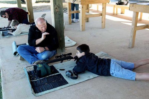Dave Davis (center) instructs Boy Scout Jared Barham on a Fort Campbell firing range Oct. 16th. Scouts from the Middle Tennessee Council received weapons training from volunteers to earn their Rifle Merit Badge.  (Photo by Spc. Kelly Fox)