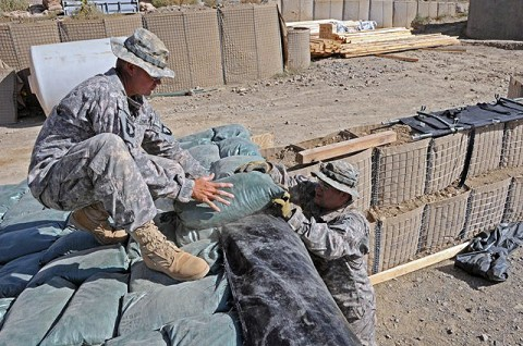 U.S. Army Sgt. David A. Ramirez, the noncommissioned officer in charge of mortar operations from Company D, 2nd Battalion, 506th Infantry Regiment, 4th Brigade Combat Team, 101st Airborne Division, and native of San Antonio, and U.S. Army Pfc. Armando J. Ramos, a mortarman with D Co., 2-506th Inf. Reg., 4th BCT, 101st Airborne Div., and native of Victorville, CA, reinforce a mortar fighting position Sept. 27th on Combat Outpost Munoz. (Photo by U.S. Army Spc. Luther L. Boothe Jr., Task Force Currahee Public Affairs Office)