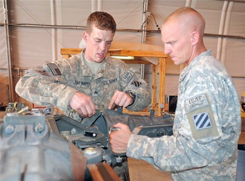 U.S. Army Sgt. Craig Hayward, powertrain mechanic and native of Huntingtown, MD, assigned to Company D, Task Force Viper works to disassemble a rotor head from an AH-64 Apache helicopter on Forward Operating Base Salerno while U.S. Army Sgt. James Elliot, turbine engine mechanic from Millbrook, AL, assigned to D Co., TF Viper, provides assistance. (Photo by U.S. Army Staff Sgt. Brent C. Powell, 3rd Brigade, 101st Airborne Division)