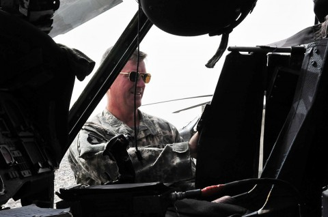 Chief Warrant Officer 4 Merle Goodall, Task Force Eagle Assault UH-60 Blackhawk standardization instructor pilot, demonstrates the difficulties pilots have trying to force the aircraft''s pilot ballistic armor wing panel to retract after dirt has jamming the gliding mechanism.