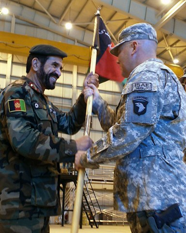 U.S. Army Brig. Gen. Warren Phipps (right), deputy commanding general (support) for the 101st Airborne Division, passes the Combined Action Program guidon to Afghan Brig. Gen. Mohammed Barat, Kabul Wing commander of the Afghan Air Force. (Photo by U.S. Army Sgt. Monica K. Smith, 3rd Combat Aviation Brigade, Task Force Falcon)