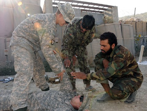 U.S. Army Spc. Jon C. Humphries, a combat medic , and U.S. Army Spc. Christopher M. Tobin, a combat medic, demonstrate to Afghan National Army soldiers the proper way to check a casualty for bleeding during a class hosted by the combat medics for the ANA Sept. 27th on Combat Outpost Munoz. (Photo by U.S. Army Spc. Luther L. Boothe Jr., Task Force Currahee Public Affairs Office)