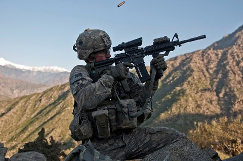 U.S. Army Spc. Brit B. Jacobs, a combat medic from Sarasota, FL, assigned to Company C, 2nd Battalion, 327th Infantry Regiment, Task Force No Slack, fires his M4 rifle from a remote hilltop in the Shal Valley in eastern Afghanistan's Nuristan Province Nov. 7th at the beginning of an eight-hour firefight against insurgents. (Photo by U.S. Army Staff Sgt. Mark Burrell, 210th Mobile Public Affairs Detachment)