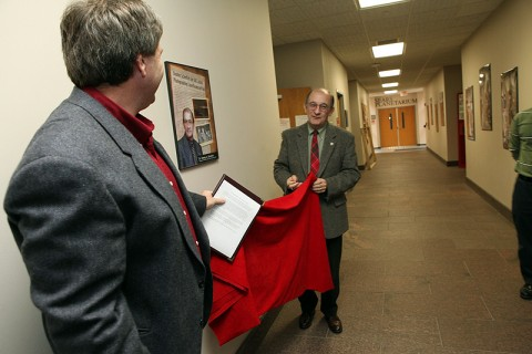Dr. Jamie Taylor (left), dean of the Austin Peay State University College of Science and Mathematics, and Dr. Dewey Browder, chair of the APSU Department of History and Philosophy, unveil a framed poster to honor Browder during the 50th anniversary of the laser. Browder is the first to photograph successfully a laser beam. (Photo by Bill Persinger, APSU Public Relations and Marketing)