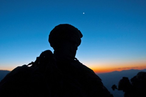 A Soldier from Bushmaster Company, Task Force Bulldog takes a short breather on a mountainside at about 7,000 feet as the sun rises over the Pech River Valley in eastern Afghanistan's Kunar Province Nov. 23rd. The Soldiers teamed up with members of the Afghan National Army during a month-long series of operations to clear some of the most dangerous parts of Task Force Bulldog's area of operations. (Photo by U.S. Army Staff Sgt. Mark Burrell, Task Force Bastogne Public Affairs)