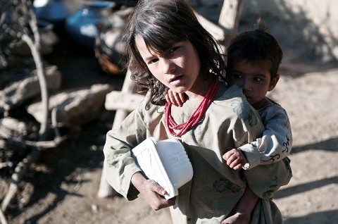 An Afghan girl clutches a box of food with one arm and her baby brother with another at a small village outcropping on a mountainside overlooking the Pech River Valley in eastern Afghanistan's Kunar Province Nov. 23rd. Soldiers from Task Force Bulldog and Afghan National Army soldiers cleared this village during Operation Bulldog Bite and handed out food to this girl and her siblings. (Photo by U.S. Army Staff Sgt. Mark Burrell, Task Force Bastogne Public Affairs)