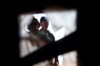 Peering through a window, an Afghan man is searched for weapons by U.S. Army Spc. Nathan H. Willett, an infantry team leader from Lynn, AR, assigned to Company B, 1st Battalion, 327th Infantry Regiment, Task Force Bulldog, during the final phase of Operation Bulldog Bite in the Pech River Valley in eastern Afghanistan's Kunar Province Nov. 23rd. (Photo by U.S. Army Staff Sgt. Mark Burrell, Task Force Bastogne Public Affairs)