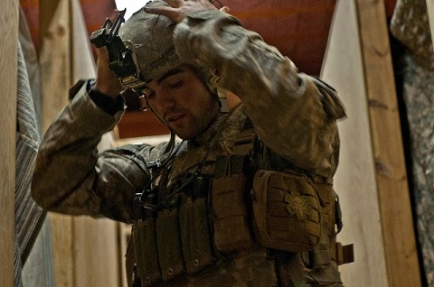 U.S. Army Spc. Brandon Brouhard, a combat medic from Modesto, CA, assigned to Company C, 2nd Battalion, 327th Infantry Regiment, Task Force No Slack, pulls on his helmet and gear to prepare for his tower guard shift at Combat Outpost Penich in eastern Afghanistan's Kunar Province Nov. 3rd. (Photo by U.S. Army Staff Sgt. Mark Burrell, 210th Mobile Public Affairs Detachment)