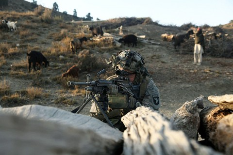 U.S. Army Pfc. Randall Kinnaman from Norman, OK, with E Company, 2nd Battalion, 506th Infantry Regiment, 4th Brigade Combat Team, 101st Airborne Division, provides security behind a log pile in a village in the Charbaran District here Oct. 27th during Task Force White Currahee Toccoa Tikurah. (Photo by U.S. Army Spc. Lorenzo Ware, Task Force Currahee Public Affairs)