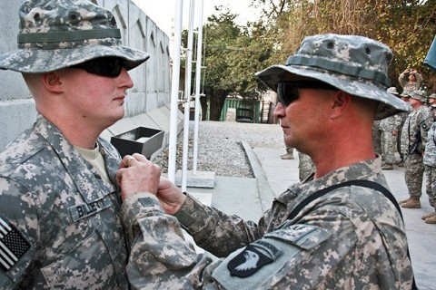 U.S. Army Sgt. William Billett (right), an infantryman with Company B, 2nd Battalion, 506th Infantry Regiment, pins the Purple Heart on the chest of his son, U.S. Army Sgt. Timothy Billett, a military policeman from Headquarters and Headquarters Company, 1st Special Troops Battalion, Thanksgiving Day on Forward Operating Base Finley Shields in eastern Afghanistan. (Photo by U.S. Army Staff Sgt. Ryan C. Matson, Task Force Bastogne Public Affairs)