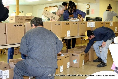 Volunteers fill boxes with food for needy families Friday