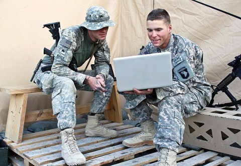 U.S. Army Sgt. Bradley J. Ragle (left), and his younger brother, U.S. Army Spc. Brandon J. V. Ragle, both of Troop A, 1st Squadron, 61st Cavalry Regiment, look at photos together on a computer outside their tent Nov. 19th at Forward Operating Base Connolly. (Photo by U.S. Army Staff Sgt. Ryan C. Matson, Task Force Bastogne Public Affairs)