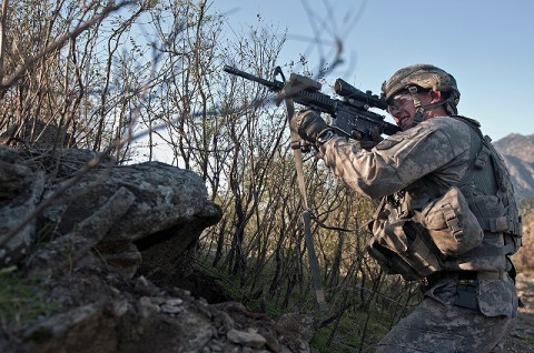 U.S. Army Spc. Brit B. Jacobs, a combat medic from Sarasota, fires his M4 rifle from a remote hilltop in the Shal Valley in eastern Afghanistan's Nuristan Province. (Photo by U.S. Army Staff Sgt. Mark Burrell, 210th Mobile Public Affairs Detachment)