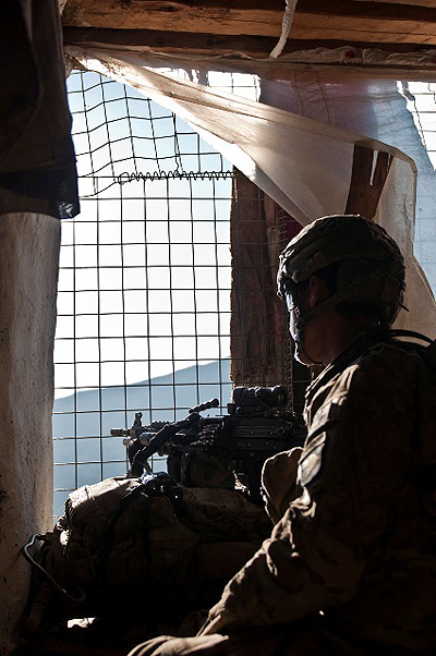 During a short break to eat and rest, U.S. Army Pfc. Chris J. Nielsen, from Huntington Beach, CA, assigned to Company B, 1st Battalion, 327th Infantry Regiment, Task Force Bulldog, stands guard at a window during joint clearing operations in the Pech River Valley in eastern Afghanistan's Kunar Province Nov. 25th. (Photo by U.S. Army Staff Sgt. Mark Burrell, Task Force Bastogne Public Affairs)