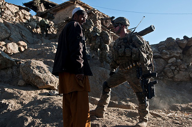 U.S. Army Sgt. John J. Nabel, from Chatsworth, NJ, Task Force Bulldog, talks with a villager while his partners from the Afghan National Army, search the rest of the area during joint operations in the Pech River Valley in eastern Afghanistan's Kunar Province Nov. 24th. The three-day operation cleared a mountainside that was suspected of insurgent activity. (Photo by U.S. Army Staff Sgt. Mark Burrell, Task Force Bastogne Public Affairs)
