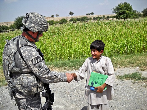 U.S. Army Staff Sgt. Robert Pharris, a ruminant specialist with the Khogyani District Agricultural Development Team attached to Company D, 1st Battalion, 138th Infantry Regiment from Mansfield, MO, talks with the son of an Afghan farmer in Chaparhar.  (Courtesy photo)