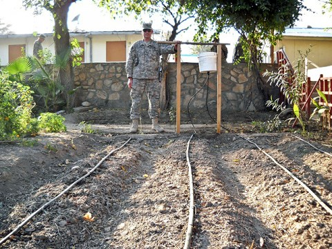 U.S. Army Staff Sgt. Robert Pharris, a ruminant specialist with the Khogyani District Agricultural Development Team attached to Company D, 1st Battalion, 138th Infantry Regiment from Mansfield, MO, stands beside a drip irrigation system the ADT constructed on Forward Operating Base Finley Shields. The system supplies water directly to the roots of plants, thereby conserving water and maximizing growth. (Courtesy photo)