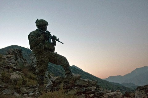 """As the sun begins to rise, U.S. Army Staff Sgt. McCarthy Phillip, an infantry squad leader from Decatur, GA, assigned to Company C, 1st Battalion, 327th Infantry Regiment, Task Force Bulldog, scans the Pech River Valley for insurgent movement in eastern Afghanistan's Kunar Province Nov. 20th. """"We're up here doing an over watch and trying to stop any type of movement in the trails,"""" said Phillip. (Photo by U.S. Army Staff Sgt. Mark Burrell, Task Force Bastogne Public Affairs Office)"""