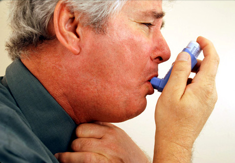 A man with COPD takes a shot from his inhaler