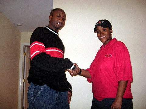 "Richard ""Reason"" Garrett shaking hands with Sherry Walcott moments after entering her new home."