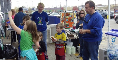 Sango Elementary Teacher and Recycle Team Sponsor Tonya Campbell look on as members of the recycle team quiz the Maynard Family on their recycle knowledge.