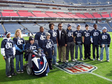NFL Play60 Students on the field with Titans Head Coach Jeff Fisher.
