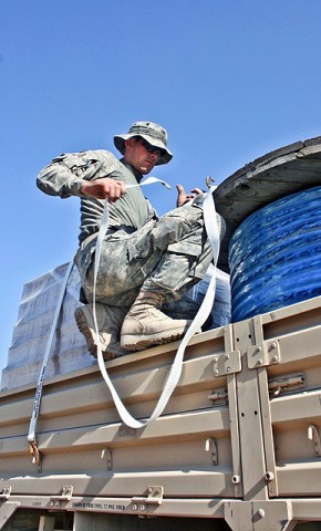 A McQueeney, Texas, native, U.S. Army Spc. Garrett Bartlett secures the load on his light medium tactical vehicle trailer with cargo straps Nov. 17th at Forward Operating Base Fenty before taking the drive back to FOB Connolly. (Photo by U.S. Army Staff Sgt. Ryan C. Matson, Task Force Bastogne Public Affairs)