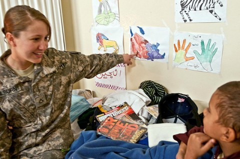 """U.S. Army Pfc. Deana Hilburn, a medic from Atoka, OK, laughingly asks Abas, a 9-year-old Afghan boy, """"Who's the pig?"""" during her bedside visit with him Nov. 30th at the 426th Brigade Support Battalion Aid Station on Forward Operating Base Fenty. Hilburn and the other medics assigned to 426th Bde. Support Bn. have been treating Abas for severe burns to both legs. (Photo by U.S. Army Staff Sgt. Ryan C. Matson, Task Force Bastogne Public Affairs)"""